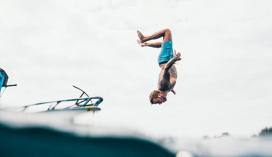 man wearing blue shorts about to dive on body of water