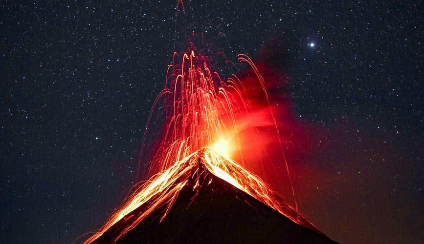 volcano erupting at night under starry sky