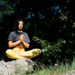photo of woman doing yoga while sitting on rock